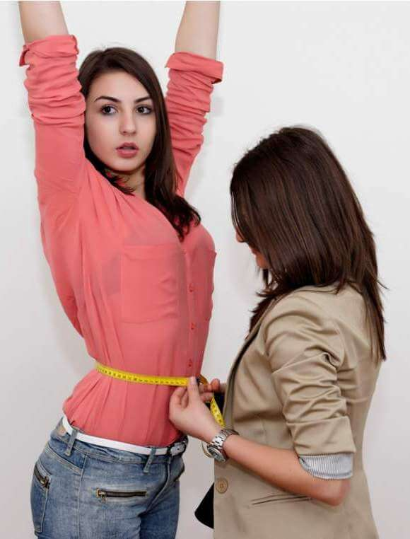 young-woman-measuring-waist-of-smiling-girlfriend-with-measuring