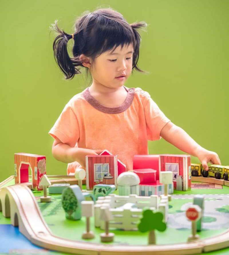 Child girl playing wooden train