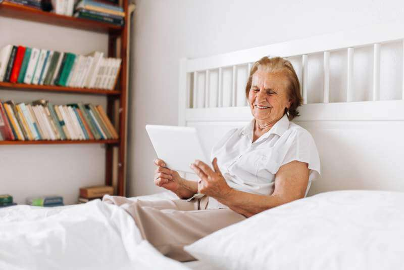 Elderly woman sitting comfortably on bed and using her tablet