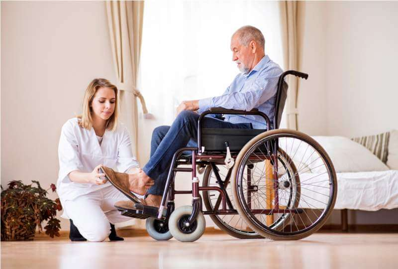 Nurse and senior man in wheelchair during home visit