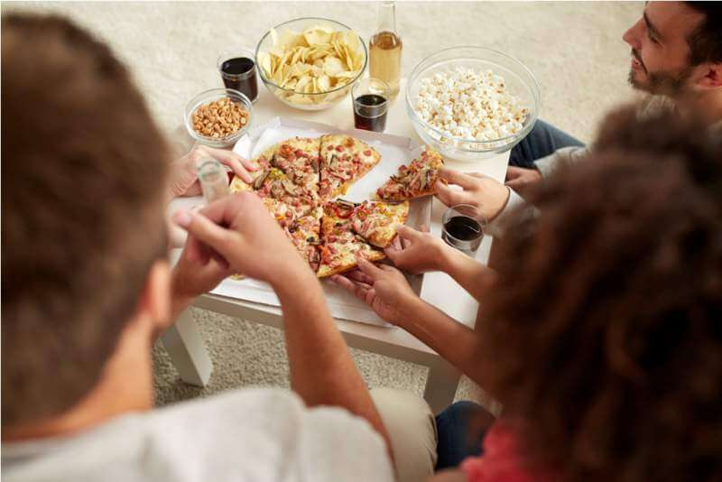 happy-friends-with-drinks-eating-pizza-at-home