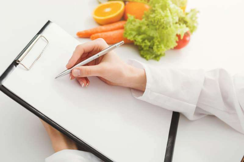 nutritionist-doctor-writing-diet-plan-on-table