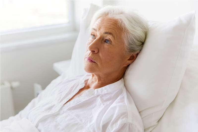 sad-senior-woman-lying-on-bed-at-hospital-ward