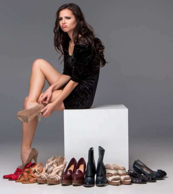 sitting woman trying on high heeled shoes