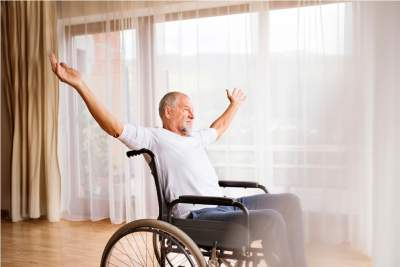 Senior man sitting on wheelchair at home