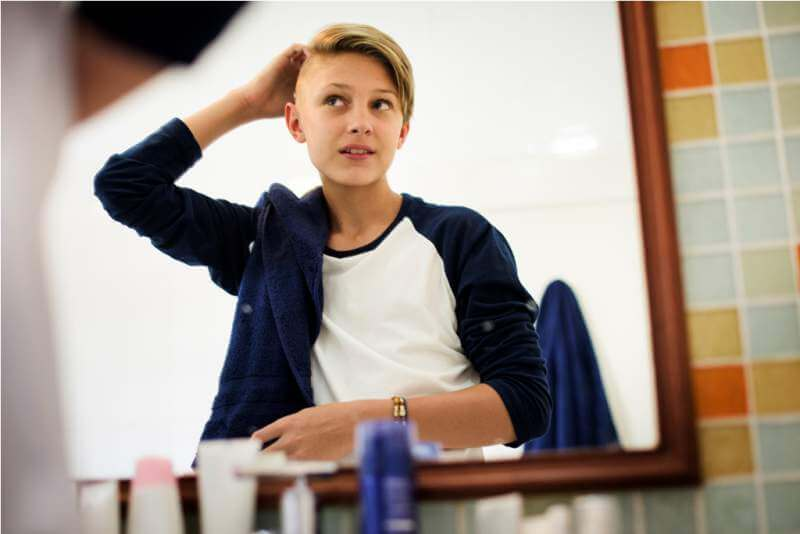Young caucasian boy set hair with mirror in bathroom