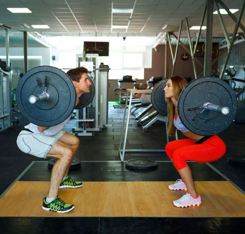 athletic-man-and-woman-with-barbell-doing-squats