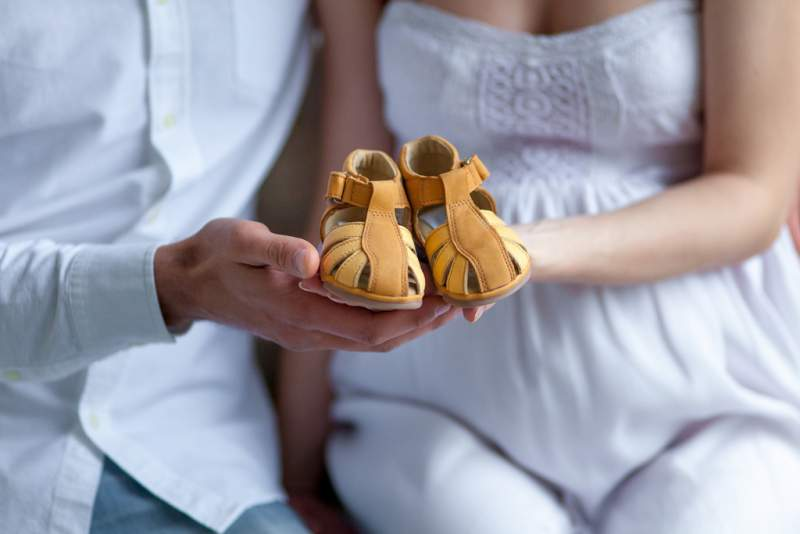 cheerful-young-couple-with-baby-shoes-sitting
