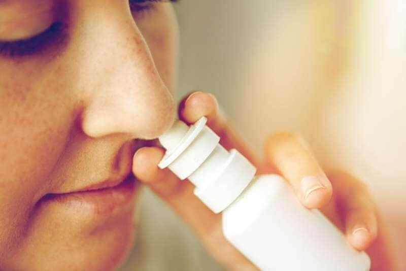 close-up-of-sick-woman-using-nasal-spray