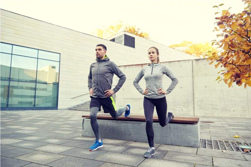 couple-doing-lunge-exercise-on-city-street