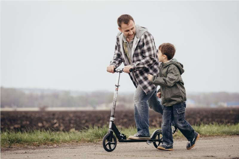 father-and-son-walking-on-the-road-at-the-day