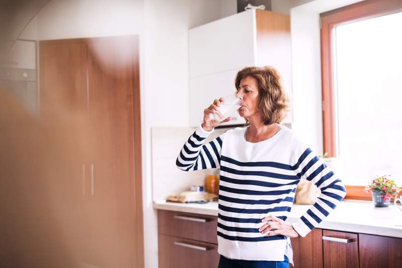 senior-woman-drinking-water-in-the-kitchen