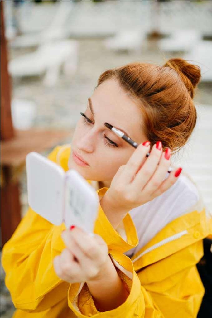 woman-doing-makeup-outside