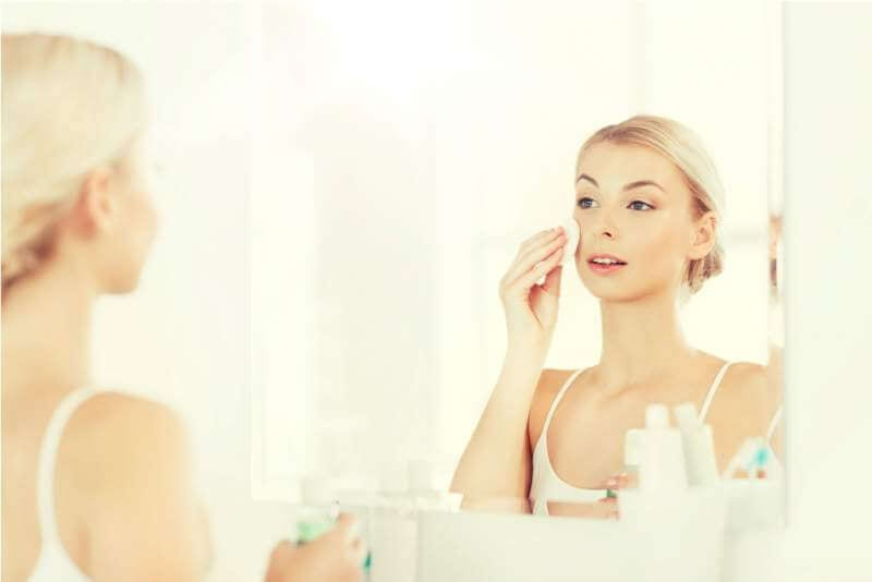 young-woman-with-lotion-washing-face-at-bathroom