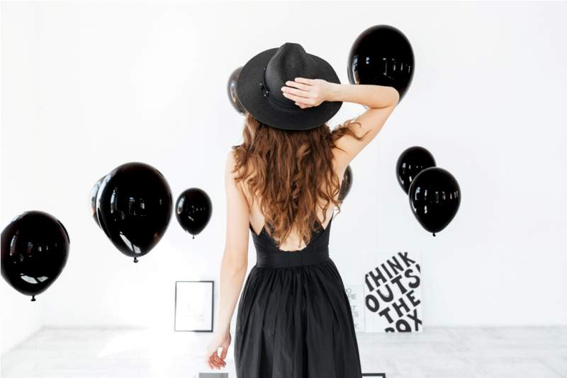 back-view-of-woman-in-black-hat-with-air-balloons