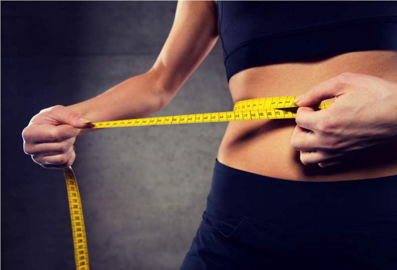 close-up-of-woman-measuring-waist-by-tape-in-gym