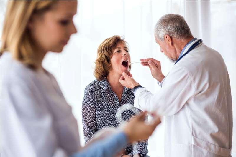 senior-doctor-examining-a-senior-woman-in-office