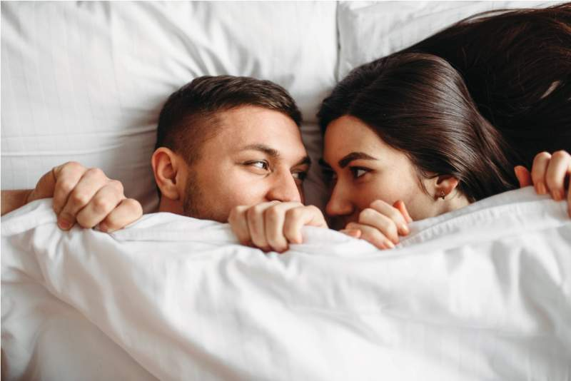 shy-love-couple-lies-on-big-white-bed