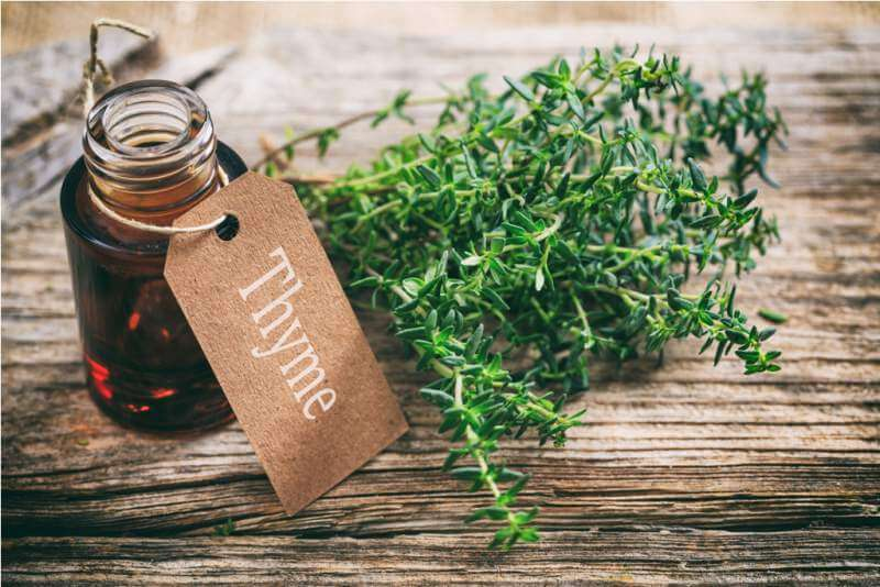 thyme-oil-on-wooden-background
