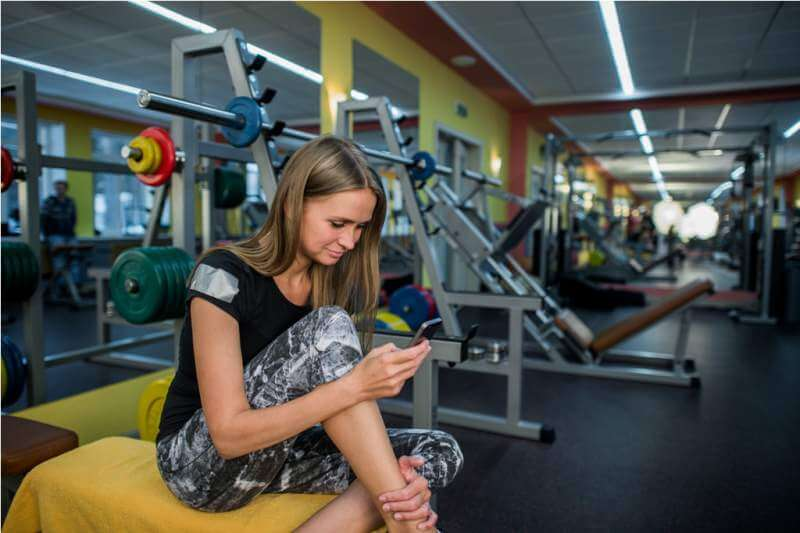young-woman-using-phone-in-gym
