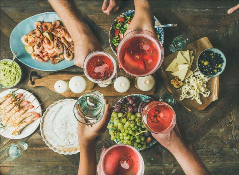 flat-lay-of-friends-hands-eating-and-drinking