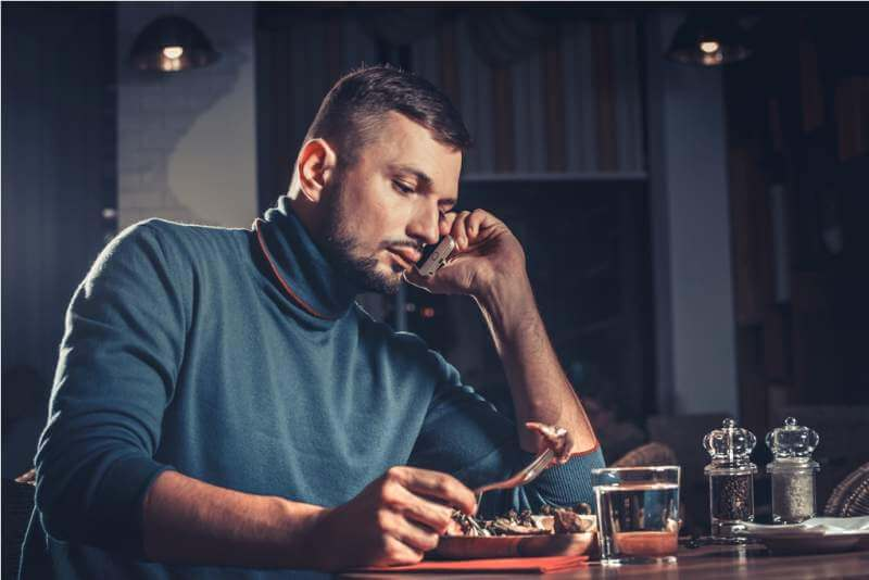 man-eating-and-speaking-on-mobile-phone