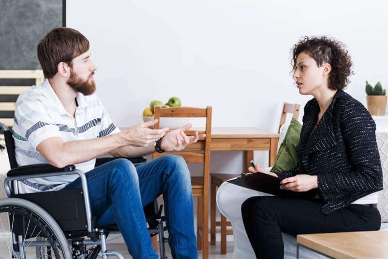 man-in-wheelchair-talking-with-psychotherapist
