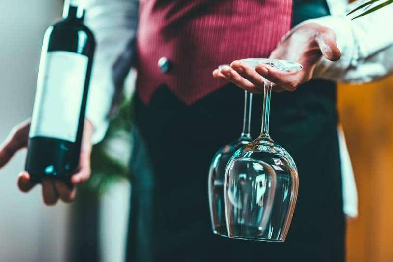 sommelier-holding-wine-bottle-and-wine-glasses