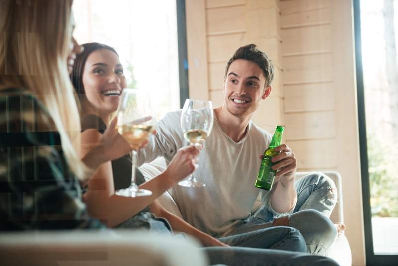 cheerful-young-friends-drinking-wine-and-beer