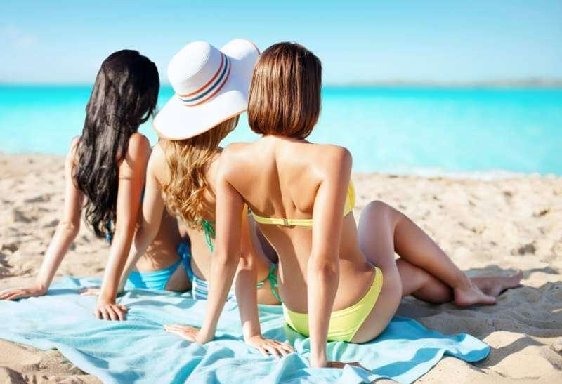 group-of-women-in-swimwear-sunbathing-on-beach