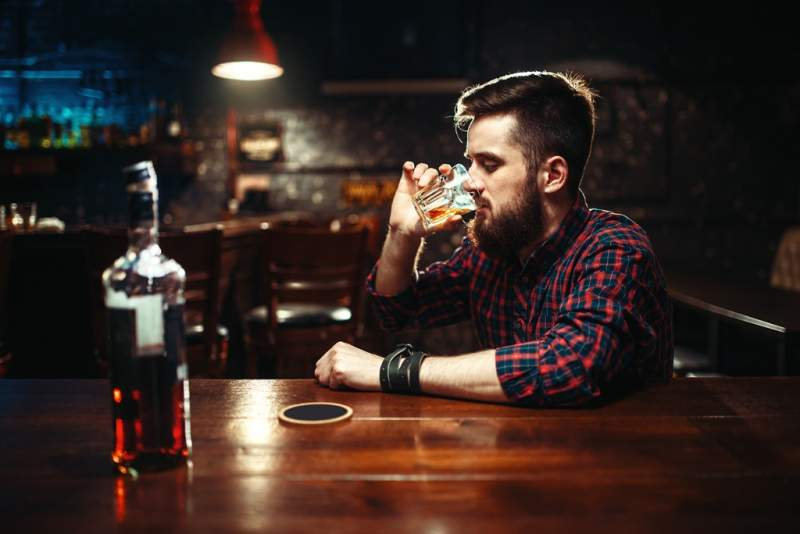 man-sitting-at-the-bar-and-drink-strong-alcohol