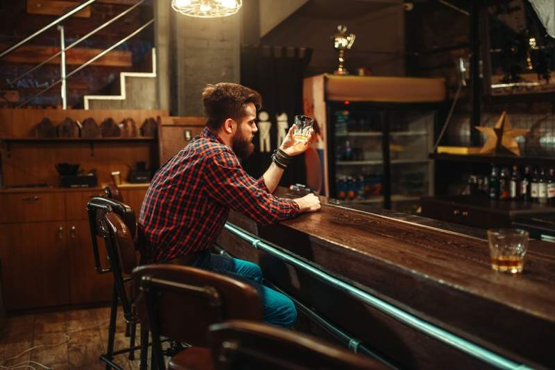 man-sitting-at-the-bar-counter-and-drink-alcohol
