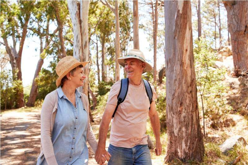 mature-couple-hiking-along-forest-path-together
