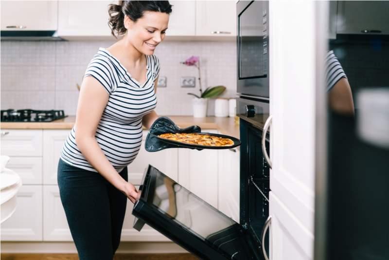 portrait-of-pregnant-woman-preparing-pizza