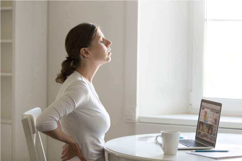 profile-portrait-of-a-woman-at-desk-stretching