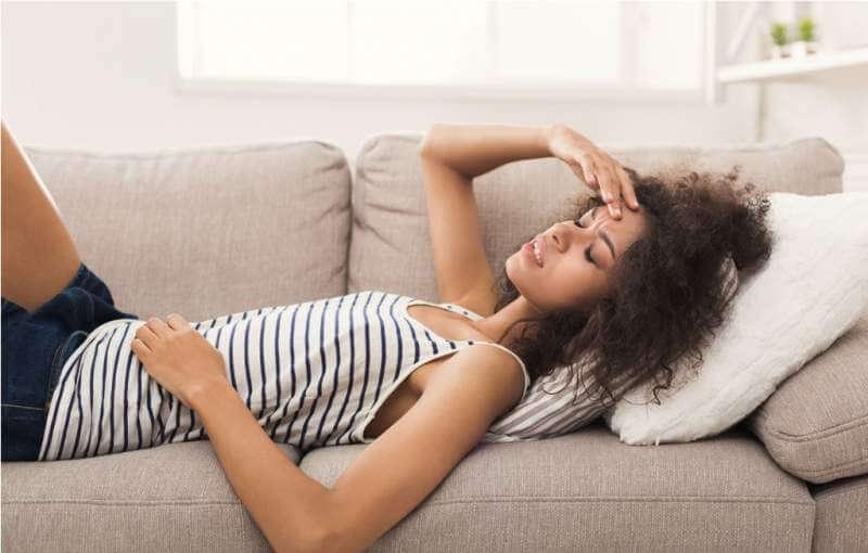 sad-black-girl-feeling-pain-lying-on-sofa