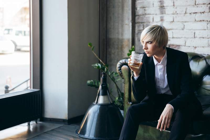 stylish-blonde-girl-drinking-alcohol-in-a-cafe