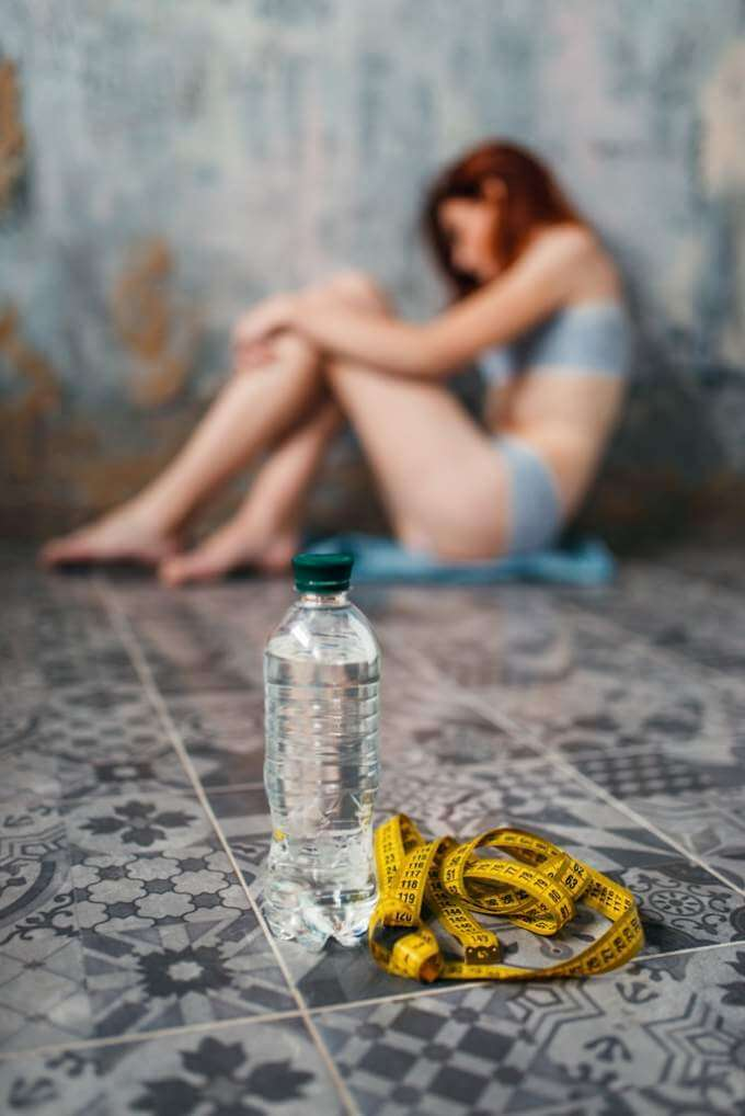 water-and-measuring-tape-against-anorexic-woman