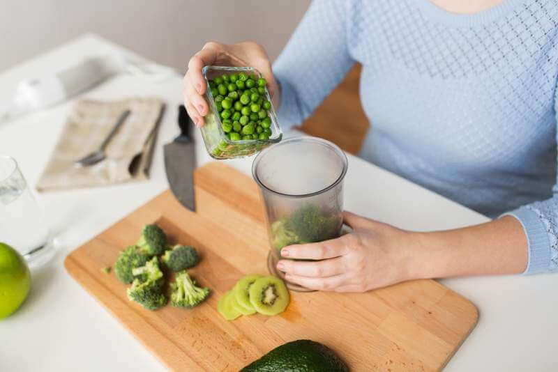 woman-hand-adding-pea-to-measuring-cup