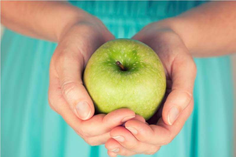 womans-hands-holding-a-green-apple
