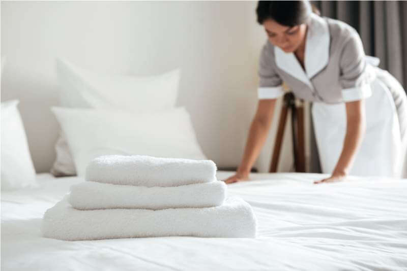 young-hotel-maid-setting-up-pillow-on-bed