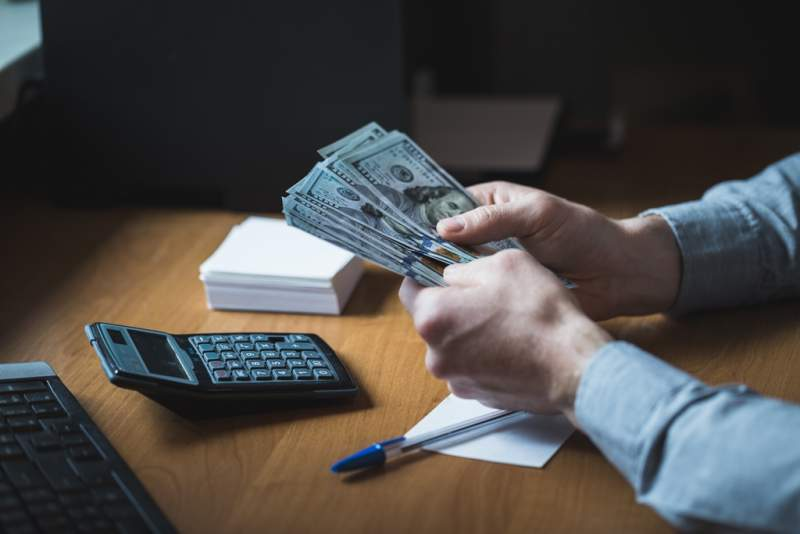 businessman-is-counting-dollars-banknotes
