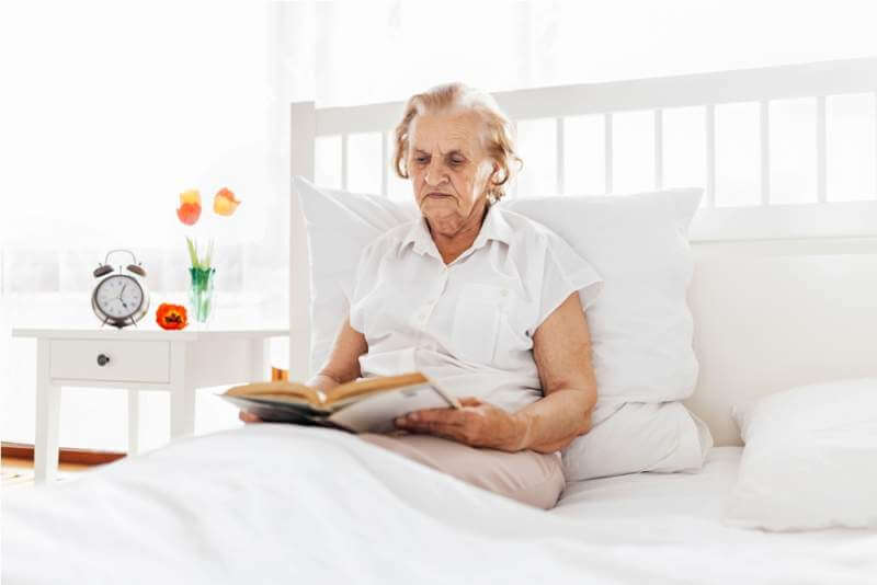 elderly-woman-sitting-comfortably-in-bed-reading