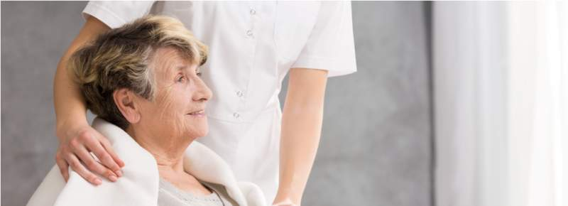 nurse-standing-behind-senior-woman