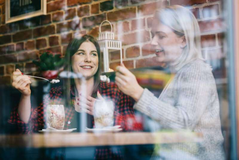 two-women-eating-and-talking-in-a-restaurant