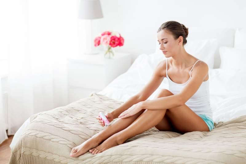woman-with-epilator-removing-hair-on-legs-at-home