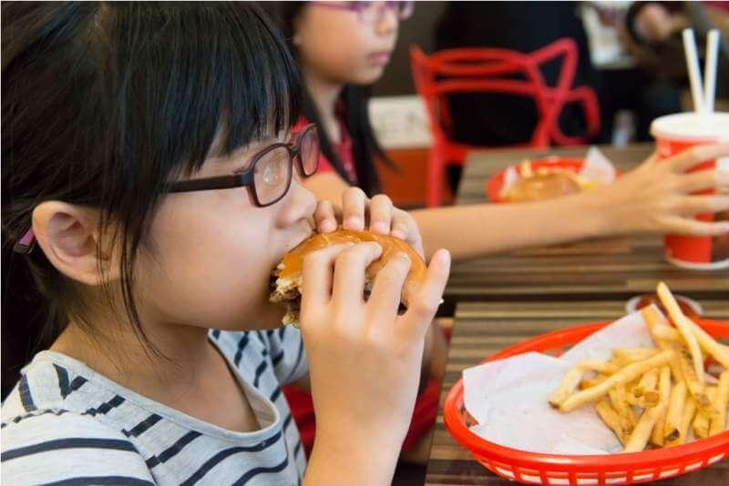 asian-kid-eating-a-hamburger-and-french-fries
