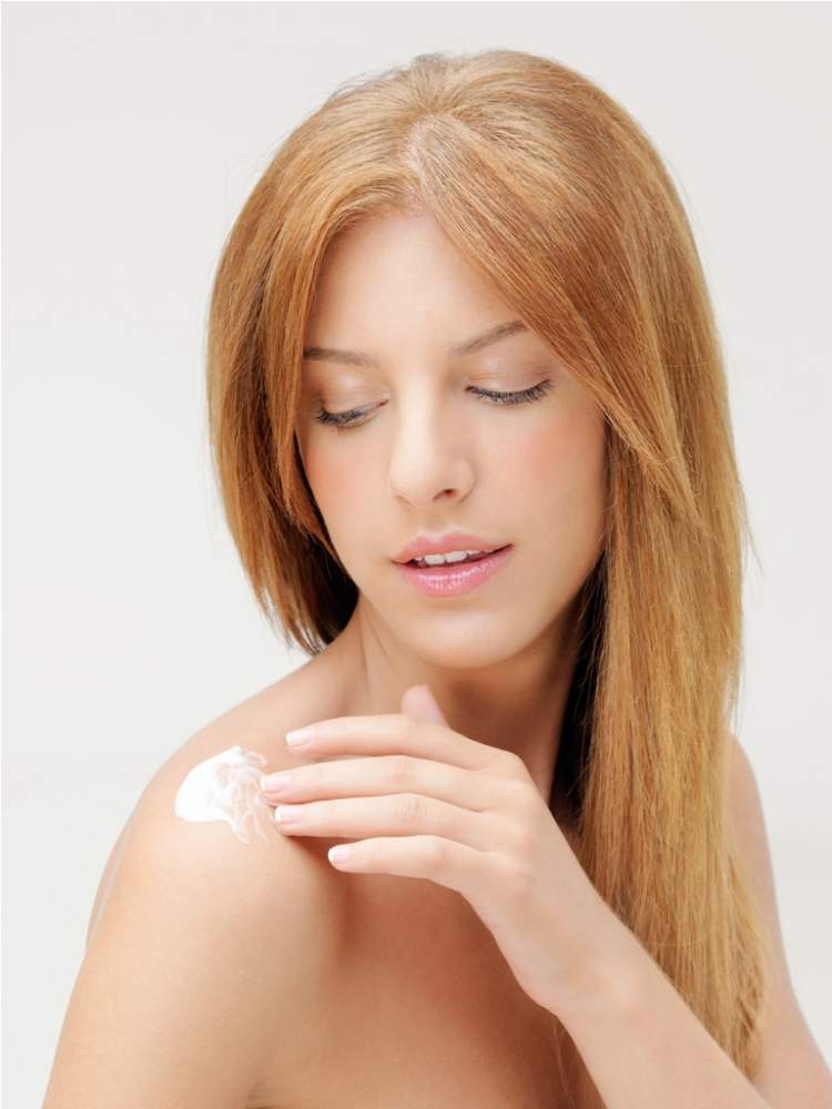 blonde-woman-applying-body-lotion-on-shoulder