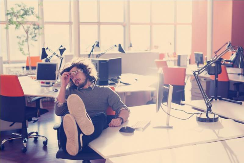 businessman-sitting-with-legs-on-desk