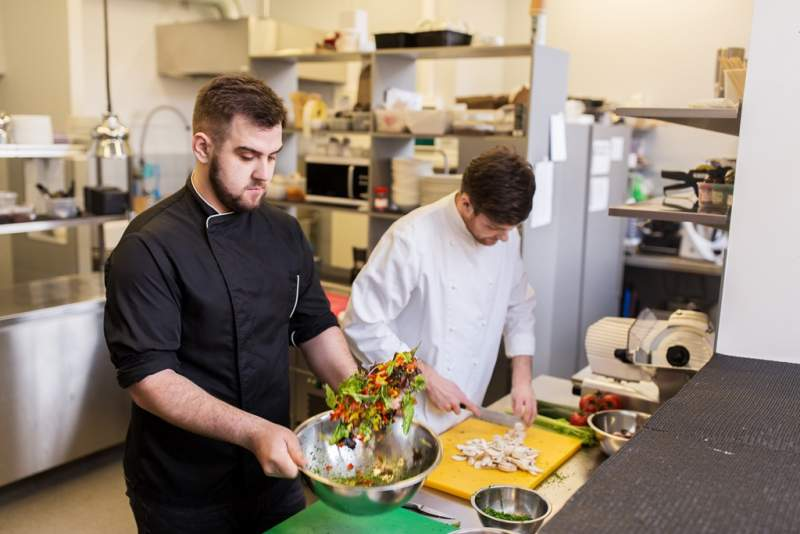 chef-and-cook-cooking-food-at-restaurant-kitchen